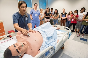 High school students take turns discovering high-fidelity mannequin simulators at the 2016 Health Careers Institute for High School Students.